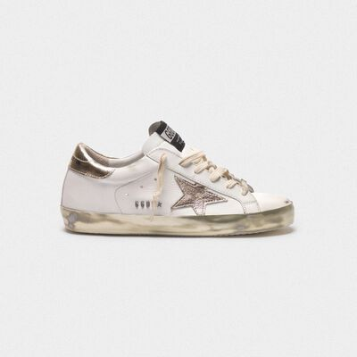 Superstar sneakers with gold sparkle foxing and metal stud lettering