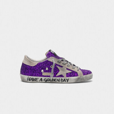 Superstar sneakers with purple glitter and lettering on the foxing